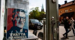 A sign with a portrait of state epidemiologist Anders Tegnell is hanged at an entrance to a restaurant to instruct people to wash their hands in Sodermalm, Stockholm. Photograph Jonathan Nackstrand/AFP