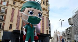 "A six-metre  statue  of a ""superhealthworker"" in Madrid to pay tribute to those  fighting   coronavirus.  Photograph: Gabriel Bouys/AFP via Getty Images"