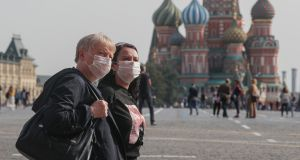 People wearing   face masks walk on the Red Square in Moscow. The city   reported 1,560 new coronavirus cases on Friday and Russia registered 7,212 new infections – the highest such daily figures in three months. Photograph: Sergei Ilnitsky/EPA