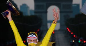 Slovenian rider Tadej Pogacar of the UAE Team Emirates poses with his Tour de France trophy with  Arc de Triomphe in the background. Photograph: Stephane Mantey/EPA