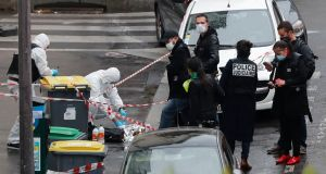 Police officers gather in the area of a knife attack near the former offices of satirical newspaper Charlie Hebdo on Friday in Paris. Photograph: AP