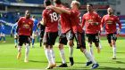 Manchester United celebrate Bruno Fernandes's last-minute winner against Brighton. Photograph: Glyn Kirk/Getty