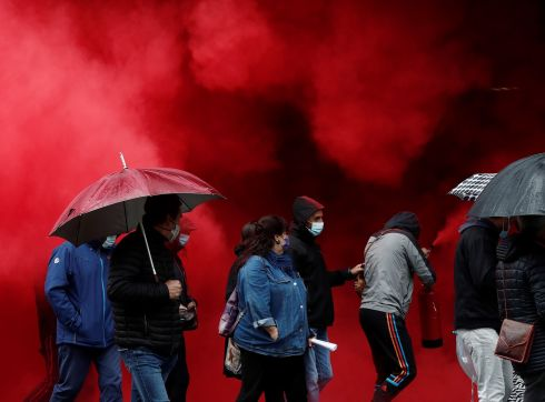 "'GATHER AND FIGHT': Protesters move through red smoke deployed during a demonstration called by the LAB union and Basque political grouping Ernai under the motto ""Gather and fight for employment, lives and the future"", in Pamplona, Spain. Photograph: Jesus Diges/EPA"