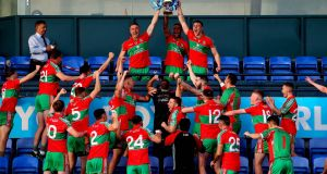 Ballymun Kickhams' Paddy Small, James McCarthy and John Small lift the trophy. Photograph: Ryan Byrne/Inpho