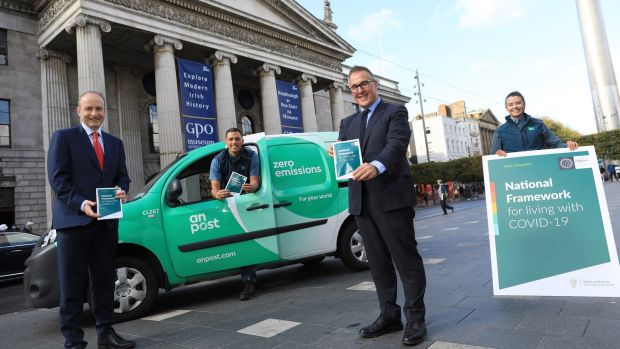 Taoiseach Micheal Martin launching the National Framework for Living with Covid-19 Information Leaflet with An Post CEO David Redmond and employees Laura Fitzsimons and Keith Lally outside the GPO, Dublin. Photograph: Julien Behal Photography/PA Wire