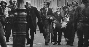 A file picture from Bloody Sunday in Derry on January 30th, 1972. Father Edward Daly and others are seen running down the street with an injured man after soldiers opened fire on protestors.