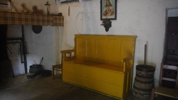 Settle bed shown closed up (containing its bedding) for use as a fireside bench. The seat of this popular design also folds outwards, to create a floor-level, high-sided double bed. Photograph: Claudia Kinmonth, courtesy Bunratty Folk Park, Shannon Heritage