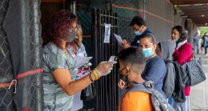 Students complete a temperature check before entering their first day of the school year for elementary classrooms at Public School 102 in Queens. New York City. Photograph: Sarah Blesener/The New York Times