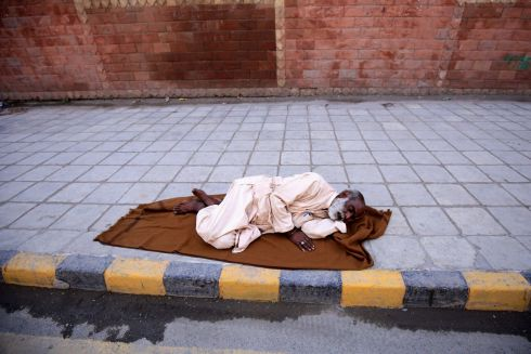 LEFT BEHIND: An elderly Pakistani man sleeps on a road side in Peshawar, Pakistan, on International Day for Old Persons. Photograph: Arshad Arbab/EPA