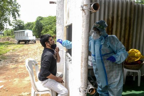 INDIA: A health worker wearing personal protective equipment collects a swab sample from a resident for a Covid-19 test at a temporary collection centre in Secunderabad, the twin city of Hyderabad. Photograph: Noah Seelam/AFP via Getty Images
