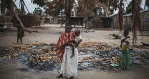 A woman holds her younger child while standing in a burned out area in the recently attacked village of Aldeia da Paz outside Macomia, Mozambique. Photograph:  Marco Longari/AFP