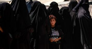 A boy stands in line with women to receive aid at the Kurdish-run al-Hol camp in northeastern Syria, where families of Islamic State foreign fighters are held. Photograph: Delil Souleiman/AFP via Getty Images