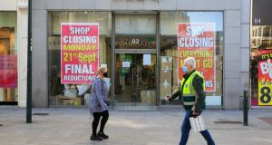 People wearing face mask pass closed down stores on Grafton Street. Photograph: Gareth Chaney/Collins