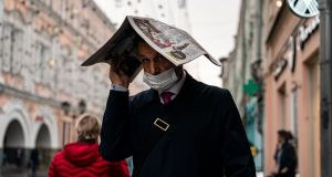 A man wearing a face mask uses a newspaper to protect himself from the rain in central Moscow on Thursday. Photograph:   Dimitar Dilkoff/AFP via Getty Images