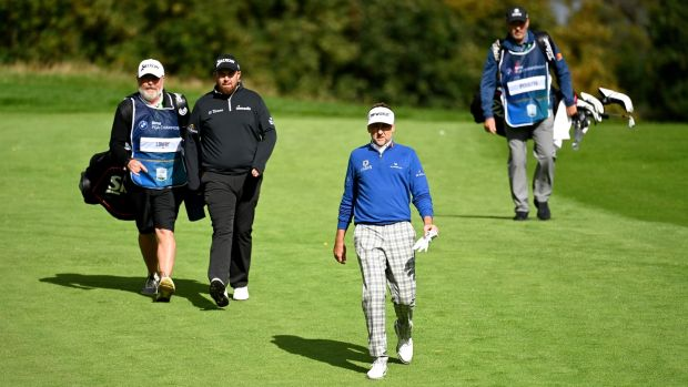 Ian Poulter and Shane Lowry walk down the fourth fairway on the final day. Photo: Ross Kinnaird/Getty Images