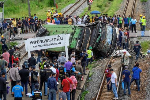 CRASH: Officials and onlookers gather near the wreckage of an overturned bus involved in a deadly collision with a train next to Khlong Kwaeng Klan railway station in Chachoengsao province, east of the Thai capital Bangkok, on October 11th. Photograph: Mladen Antonov/AFP via Getty