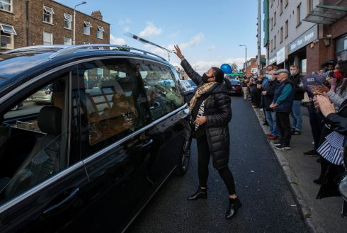CELEBRATED ACTIVIST: Mourners throw flowers onto a hearse carrying the remains of veteran community activist Fergus McCabe at Summerhill, Dublin, en route to Glasnevin Cemetery, during his funeral. Photograph: Colin Keegan/Collins Dublin