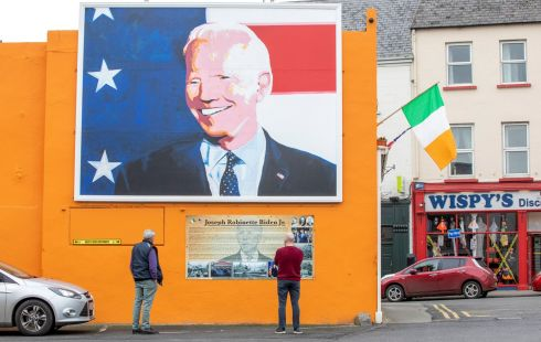 "UNCLE JOE: Bypassers read a mounted information board beneath a giant painting of Democratic US presidential candidate Joe Biden, erected in his ancestral home of Ballina, Co Mayo. ""Obviously we're 100 per cent behind Joe Biden,"" Laurita Blewitt, the former vice-president's third cousin, told AFP. Photograph: Paul Faith/AFP/Getty"