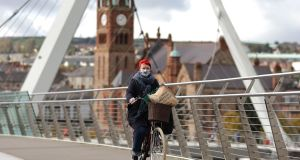 A woman cycles across the Peace Bridge over the River Foyle in Derry. The highest incidence of the disease is in the Derry and Strabane council area which over the past week saw 970 cases per 100,000 of the population. Photograph: Liam McBurney/PA Wire