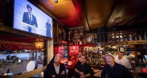 Employees of cafe Marcella in Amsterdam watch a broadcast of a press conference of the Dutch prime minister and health minister on Tuesday on new measures taken to tackle the spread of the Covid-19 pandemic. Photograph: Remko de Waal/ ANP/ AFP/Getty
