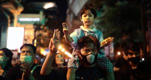A pro-democracy protester and a child hold up a three-finger salute during a demonstration in Bangkok on Thursday. Photograph: Jack Taylor/AFP via Getty Images