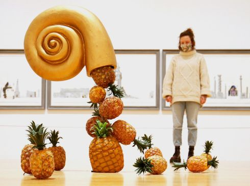 PINEAPPLE MANIA: A Tate employee stands behind Edward Allington's work From the Birth of Paradise during a photocall for the new collection displays at Tate Britain in London. Photograph: Jonathan Brady/PA Wire