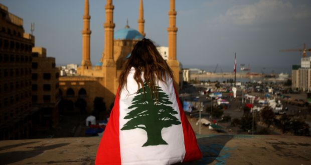 A Lebanese anti-government protester draped in a national flag sits overlooking the Mohammed al-Amin mosque and the Martyrs square in Beirut on November 14th, 2019. Photograph:  Patrick Baz/AFP via Getty Images