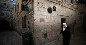 A  Palestinian woman covering her face in Jerusalem's old city.  Over half of the elderly coronavirus patients in Israel hail from the ultra-Orthodox Jewish sector. Photograph: EPA/Atef Safadi
