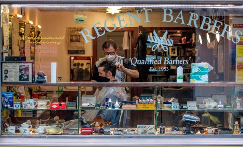 LOCKDOWN LOOMS: A barber cuts a customer's hair as both wear face masks to counter Covid-19, in a barber shop in Dublin city centre on Monday. Barber shops, hairdressers and many other businesses will be expected to shut under Level 5 restrictions intended to mitigate the spread of coronavirus, to be imposed across the Republic of Ireland this week. Photograph: Paul Faith/AFP/Getty