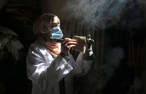 DOWN TIME: A Palestinian woman wearing a face mask amid the Covid-19 pandemic cleans artefacts at al-Qarara Cultural Museum, run by her family, after the Gaza authorities' decision to close tourist amenities to prevent the spread of coronavirus. Photograph: Said Khatib/AFP/Getty