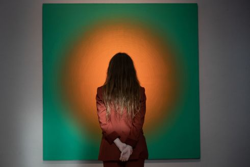 MESMERISED: A gallery assistant stands in front of a painting called Untitled, 1987 by Peter Schuyff. The work, with a guide price of £6,000-£8,000, will be put up for sale at Bonhams in London as part of the auction house's forthcoming Post-War and Contemporary Art sale, due on October 22nd. Photograph: Aaron Chown/PA Wire