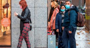 Customers wearing face masks  socially distance as they queue to enter a clothes shop in Dublin city centre on Monday, before Level 5 Covid-19 restrictions were announced. Photograph: Paul Faith/AFP/Getty