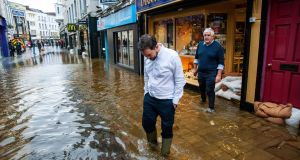 Jewellers Roland and Shane Kennedy  outside their shop in heavy flooding on Winthrop street, Cork. Photograph: Daragh Mc Sweeney/Provision