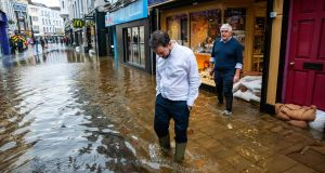 UNDER THE WEATHER: Jewellers Roland and Shane Kennedy outside their shop on Winthrop Street, Cork city, amid heavy flooding on Tuesday after the River Lee burst its banks. Photograph: Daragh McSweeney/Provision