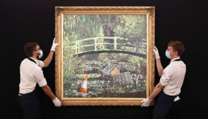 Technicians handle Banksy's Show me the Monet, a reimagining of Claude Monet's water lilies, at Sotheby's in central London.  Photograph:  Jonathan Brady/PA