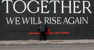 A man wearing a face  walks past a mural in Dublin on October 21st. Photograph: Paul Faith/AFP/Getty