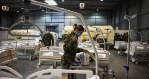 A soldier installs machines in a facility for Covid-19 patients in the Letnany Exhibition hall, Prague. Photograph:  Milan Jaros/Bloomberg