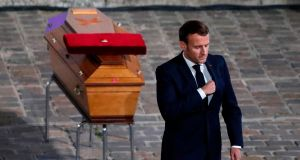 French president Emmanuel Macron pays his respects by the coffin of Samuel Paty inside Sorbonne University's courtyard in Paris. Photograph: Francois Mori/Pool/AFP via Getty Images