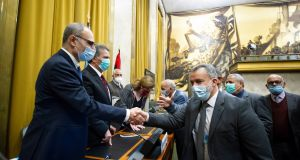 Participants shake hands after signing an agreement for a permanent ceasefire in Libya, at a UN building in Geneva, Switzerland. Photograph: Violaine Martin/EPA