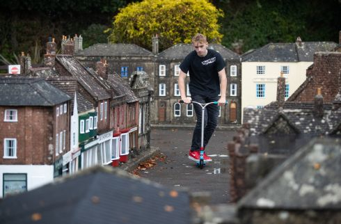 MODEL VILLAGE: Charlie Sibley from the Wimborne's StreetLight Project scooters through the streets of Wimborne Model Town and Gardens in Wimborne, Dorset. Photograph: Andrew Matthews/PA Wire