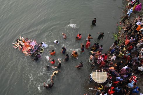 DEVOTED IN DHAKA: Devotees submerge a clay idol of the Hindu goddess Durga on the Buriganga River during the final day of the Durga Puja festival, in Dhaka, Bangladesh. Photograph: Munir Uz zaman/AFP/Getty