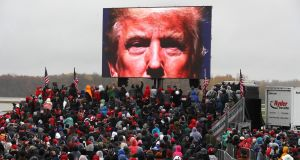 Supporters watch a video of US president Donald Trump while waiting  for his arrival at a rally at Capital Region International Airport in Lansing, Michigan. Photograph: Chip Somodevilla/Getty Images