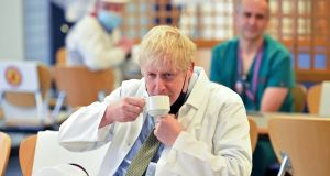 Boris Johnson pulls down his face covering to take a drink as he sits with hospital workers during his visit to Royal Berkshire NHS Hospital in Reading on Monday. Photograph: Jeremy Selwyn/AFT/Getty Images