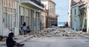 People walk past a destroyed house after an earthquake in the island of Samos on October 30th. Photograph:  STR/Eurokinissi/AFP via Getty