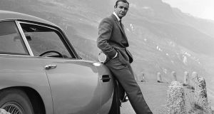Sean Connery as James Bond next to his Aston Martin DB5 in a scene from Goldfinger in 1964. Photograph: Michael Ochs Archives/Getty Images