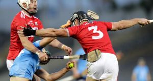 Dublin's Ronan Hayes is tackled by Colm Spillane and Tim O'Mahony of Cork. Photo: Laszlo Geczo/Inpho