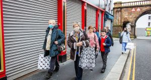 Pedestrians pass shuttered shops in Derry. The Northern Executive is to meet again on Tuesday to  discuss whether to extend the current four-week lockdown by another two weeks. Photograph: Bloomberg