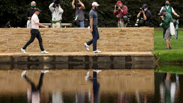 McIlroy and Dustin Johnson walk across the Hogan Bridge during their practice round. Photo: Rob Carr/Getty Images