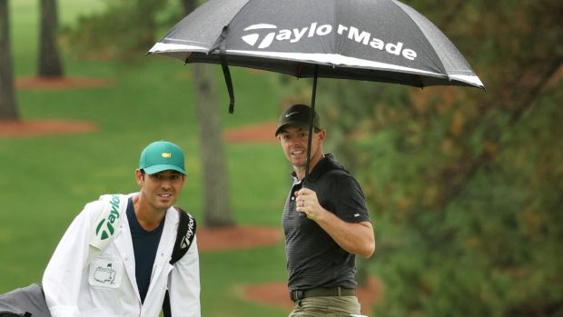 Rory McIlroy looks on from under an umbrella with caddie Harry Diamond on the seventh hole during a practice round prior to the Masters at Augusta National Golf Club. Photo: Rob Carr/Getty Images