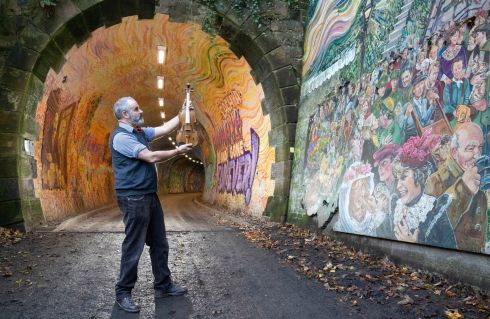 UNIQUE INSTRUMENT: Luthier Steve Burnett, at the Colinton railway tunnel mural in Edinburgh, holding a unique violin he has made during lockdown in tribute to Robert Louis Stevenson to mark the 170th anniversary since the birth of the world famous Edinburgh-born author. Photograph: Jane Barlow/PA Wire